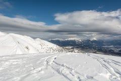 La cima della montagna con lo sci segue la conduzione giù Immagini Stock
