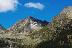 La cima della montagna sui precedenti di cielo blu Immagine Stock