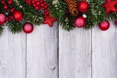 La cima rossa degli ornamenti e dei rami di Natale rasenta il legno bianco Fotografia Stock