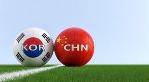 La Cina contro Partita di calcio della Corea del Sud - palloni da calcio in Cine e colori nazionali sudcoreani su un campo di cal Fotografia Stock Libera da Diritti
