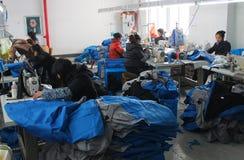 LA CINA - 15 GENNAIO: Il cinese copre la fabbrica con le cucitrici Fotografie Stock Libere da Diritti