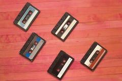 La cinta de casetes audios pone en tablón de madera rosado foto de archivo libre de regalías