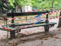 La cinta del rojo y del blanco rodea el banco recientemente pintado en Jardin de Imagenes de archivo