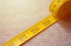 La cinta métrica amarilla con los indicadores numéricos bajo la forma de centímetros o pulgadas miente en una tela hecha punto gr foto de archivo