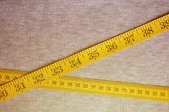 La cinta métrica amarilla con los indicadores numéricos bajo la forma de centímetros o pulgadas miente en una tela hecha punto gr imágenes de archivo libres de regalías