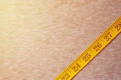 La cinta métrica del color amarillo con los indicadores numéricos bajo la forma de centímetros o pulgadas miente en una tela hech imagen de archivo