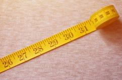 La cinta métrica del color amarillo con los indicadores numéricos bajo la forma de centímetros o pulgadas miente en una tela hech foto de archivo