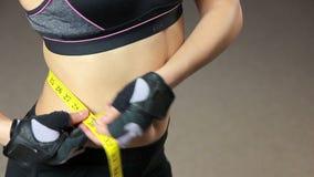 La cintura de medición de la señora delgada después del entrenamiento activo de la aptitud, pérdida de peso resulta metrajes