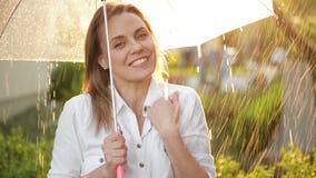 La cintura encima del retrato de la muchacha alegre que sostiene el paraguas y que coge la lluvia cae con sonrisa Ella está estir metrajes