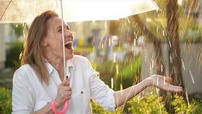La cintura encima del retrato de la muchacha alegre que sostiene el paraguas y que coge la lluvia cae con sonrisa Ella est? estir metrajes