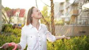 La cintura encima del retrato de la muchacha alegre que sostiene el paraguas y que coge la lluvia cae con sonrisa Ella est? estir almacen de video