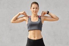 La cintura para arriba tiró de mujer deportiva guarda ambas manos en hombros, hace ejercicios durante entrenamiento de la mañana, imagen de archivo libre de regalías