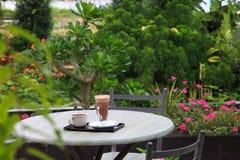 La cioccolata calda ed il tè sulla tavola di legno d'annata in caffè all'aperto fanno il giardinaggio fotografia stock libera da diritti