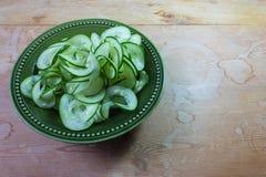 La ciotola ceramica verde con la coclea ha affettato il cetriolo su una tavola di legno stagionata Immagine Stock