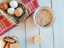 la ciotola con i fiocchi di avena, il limone, i biscotti e le uova si trovano sui bordi bianchi Fotografia Stock Libera da Diritti