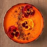 La ciotola del frullato con la pansé commestibile fiorisce, semi di chia, berrie di goji fotografia stock