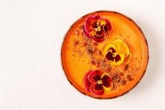 La ciotola del frullato con la pansé commestibile fiorisce, semi di chia, berrie di goji immagini stock