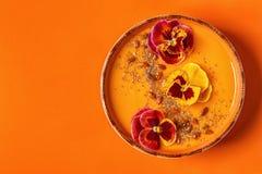 La ciotola del frullato con la pansé commestibile fiorisce, semi di chia, berrie di goji fotografie stock libere da diritti