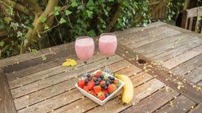 La ciotola di fragole & le bacche con una banana e una scossa bevono Fotografie Stock Libere da Diritti
