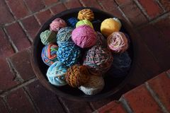 La ciotola di legno riempita di palle variopinte della mano ha filato il filato di lana Fotografia Stock