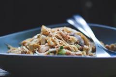 La ciotola di mein del cibo del pollo spruzzato con peperone si sfalda in una ciotola blu immagini stock