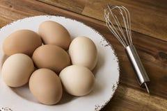 La ciotola di uova del pollo, sbatte, fondo di legno Fotografia Stock