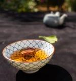 La ciotola giapponese ha riempito di tè marrone, nei precedenti una teiera deliberatamente vaga fotografia stock