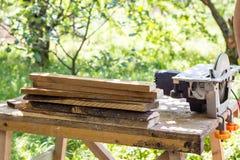 La circolare ha visto per i tronchi di albero e di legno nella fine della segheria su Elaborazione del legno per i bordi o altri  fotografia stock