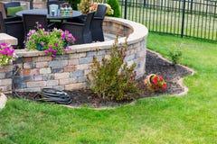 La circulaire a soulevé le patio de brique dans une pelouse verte formelle photos stock