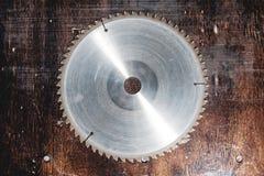La circulaire utilisée en gros plan de lame a vu sur le fond de la table en bois Atelier pour la production des produits en bois image libre de droits
