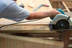 La circulaire a vu couper le morceau de bois dans l'atelier de menuiserie Images stock