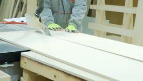 La circulaire a vu dans l'action, charpentier coupant des feuilles de contreplaqué Fabrication des meubles en bois photographie stock libre de droits