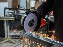 La circulaire a vu le sawing avec des étincelles Un homme travaillant avec l'outil électrique de broyeur sur la structure métalli Photographie stock libre de droits