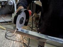 La circulaire a vu le sawing avec des étincelles Un homme travaillant avec l'outil électrique de broyeur sur la structure métalli Photo libre de droits
