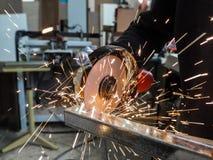 La circulaire a vu le sawing avec des étincelles Un homme travaillant avec l'outil électrique de broyeur sur la structure métalli Images libres de droits