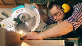 La circular profesional de las aplicaciones del carpintero vio mientras que trabajaba con madera almacen de video
