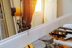 La circular vio cortar la cuchilla que moldeaba baja de madera con el detalle de la carpintería del primer del tablero con madera foto de archivo libre de regalías