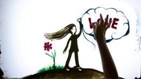 La cita inspirada, brazos del hombre dibuja a la muchacha y redacta amor con la arena de la ayuda en la pantalla