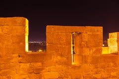 La Cite de Carcassonne, France. Carcassonne, France - October 21, 2016; city lights in distance and dark sky though battlements La Cite de Carcassonne France Stock Images