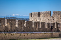 La Cite. Part of fortification of medieval city La Cite in Carcassonne with a white peaks of Pyrenees mountains stock photo