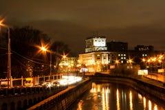 La città alla notte lungo il fiume immagini stock