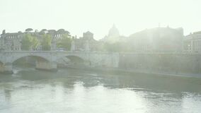 La città antica si è accesa dai fasci di luce solare, ponte attraverso il fiume, panorama di paesaggio urbano archivi video