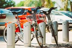 La città bikes per affitto su fondo delle automobili di parcheggio Immagini Stock Libere da Diritti