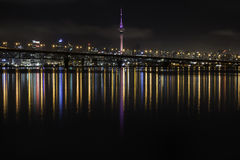 La città di Auckland ed il porto gettano un ponte sulle riflessioni variopinte di luccichio nell'acqua Fotografia Stock