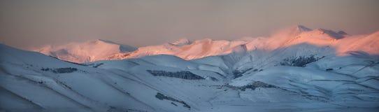 La città di Castelluccio di Norcia al tramonto, inverno con neve, Immagine Stock