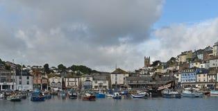 La città ed il porto a bassa marea con le barche tirate ed attraccate accanto alla replica del posteriore dorato a Brixham in Dev fotografia stock libera da diritti