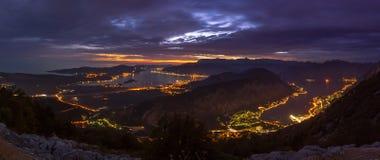 La città si accende all'ora blu nella baia di Cattaro, Montenegro immagine stock