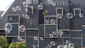 La ciudad de la cámara lenta con el jabón hincha burbujas almacen de metraje de vídeo