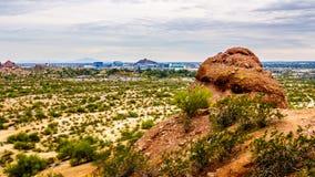 La ciudad de Phoenix en el valle del Sun visto de las motas de la piedra arenisca roja en el parque de Papago Imagenes de archivo