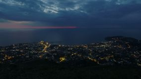 La ciudad de vacaciones cerca del mar, ciudad de la noche enciende el timelapse, visión desde el pico de montaña almacen de metraje de vídeo